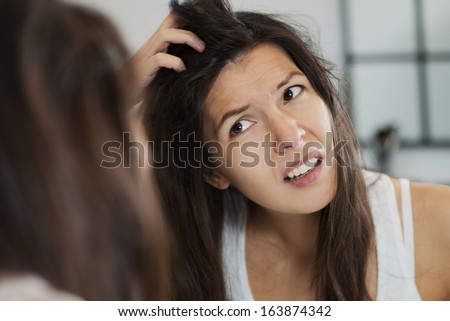 Woman having a bad hair day grimacing in disgust as she looks in the mirror and runs her hands through her hair - stock photo