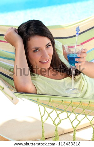 Woman having a cocktail drink in a hammock - stock photo