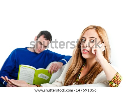 Woman having a conversation on a phone whilst a man reads in the background