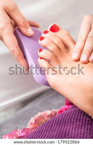 Woman having a pedicure treatment at a spa or beauty salon with the pedicurist massaging the soles of her feet with a pumice stone to cleanse dead skin and stimulate the tissue - stock photo