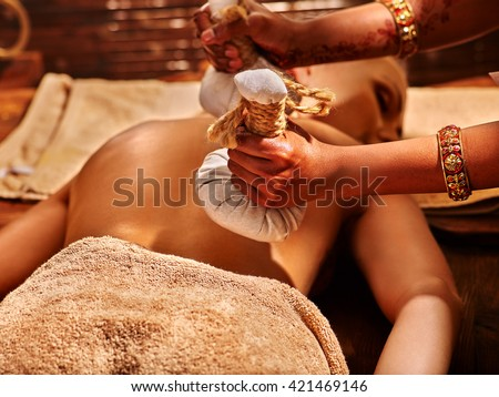 Woman having ayurvedic massage with back pouch of rice. Close up of exotic India massage. - stock photo