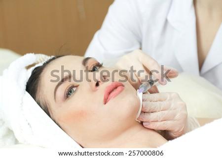 Woman Having Botox Treatment At Beauty Clinic, close up. Focus on syringe - stock photo