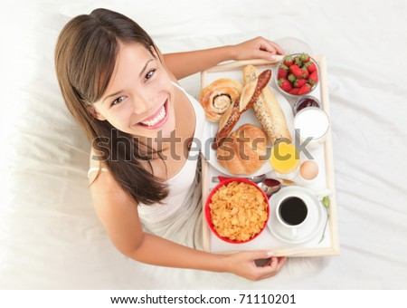 Woman having breakfast in bed. Big continental breakfast. Asian caucasian woman smiling looking at camera. - stock photo