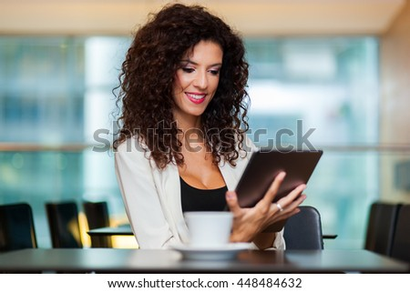 Woman having coffee and using tablet - stock photo