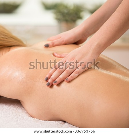 Woman having done massage in spa center - stock photo