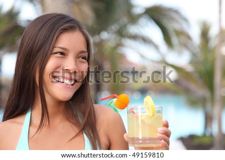 Woman having drink at tropical resort. Beautiful smiling mixed race caucasian / chinese young woman model.