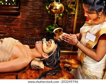 Woman having facial oil eyes mask at ayurveda spa. - stock photo