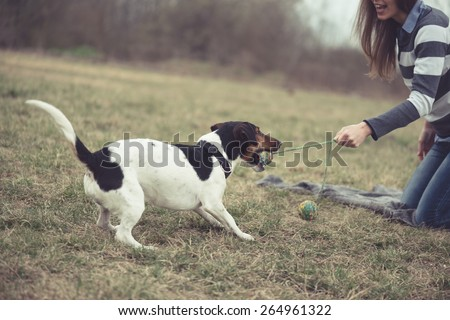 Woman having fun with her dog - stock photo