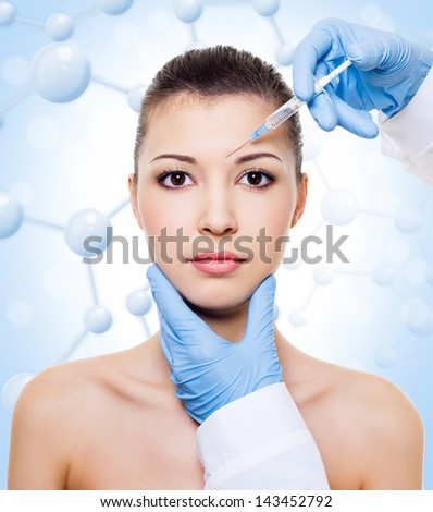 Woman having injection into the skin over molecule background - stock photo