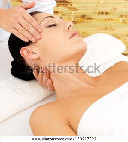 Woman having massage of face in the spa salon. Beauty treatment concept. - stock photo
