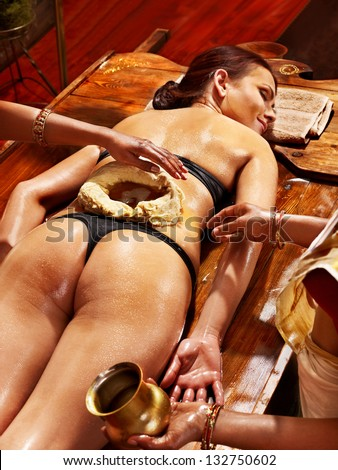 Woman having oil Ayurveda spa treatment of back pain. - stock photo