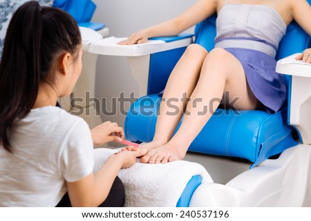 Woman having pedicure procedure in  spa salon - stock photo