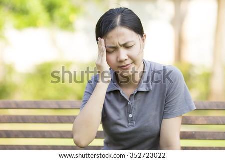 Woman Headach at Park - stock photo