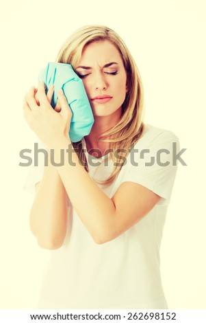 Woman heaving tooth ache, holding ice bag - stock photo