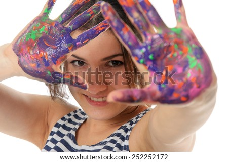 Woman held out her hands painted in colorful paint and laughing isolated against background - stock photo