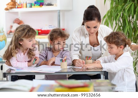 Woman helping a group of girls with their homework - stock photo
