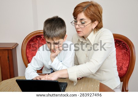 Woman helping a young boy with laptop to do his homework - stock photo