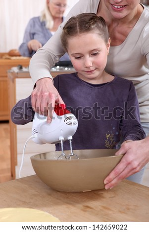 Woman helping her daughter use a hand mixer - stock photo