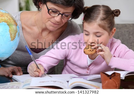 Woman helping her granddaughter with her homework - stock photo