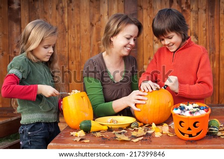 Woman helping kids to carve their pumpkin Halloween jack-o-lantern - stock photo