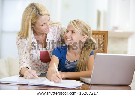 Woman helping young girl with laptop do homework in dining room - stock photo