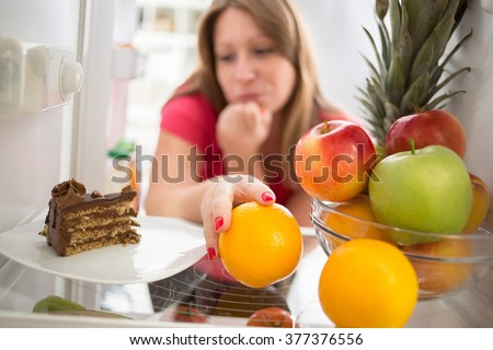 Woman hesitating whether to eat piece of chocolate cake or orange  - stock photo