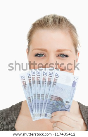 Woman hiding a middle of her face with euro banknotes against white background