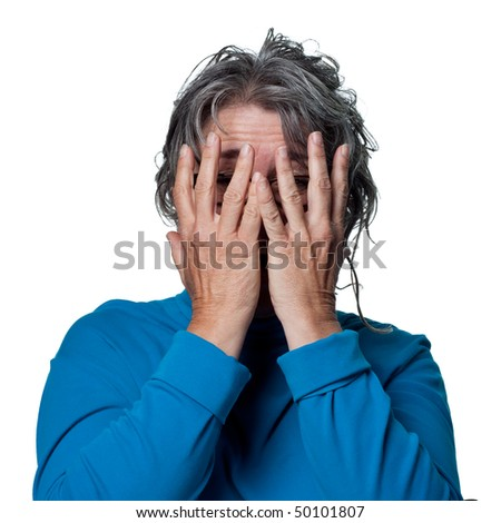 Woman hiding behind her hands, scared of seeing something - stock photo