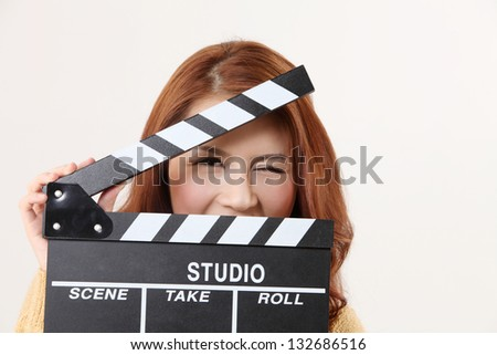 woman hiding behind the film slate - stock photo