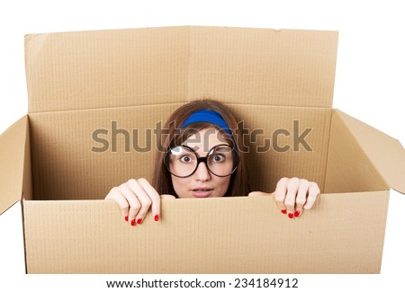 Woman hiding in a moving box - stock photo