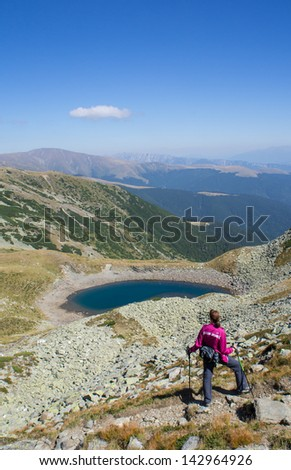 Woman hiker enjoying the view near a lake in the mountains - stock photo