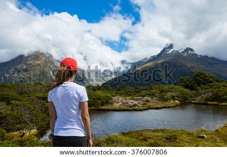 Woman hiker enjoys the view of Key Summit with Ailsa Mountain at the background. Routeburn Track, New Zealand - stock photo