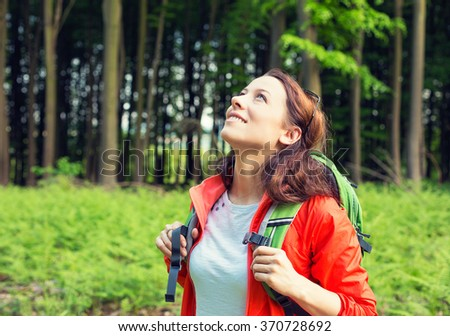 Woman hiker in forest smiling looking up enjoying freedom. Positive human emotion face expression feeling life perception success, peace of mind concept. Free happy girl