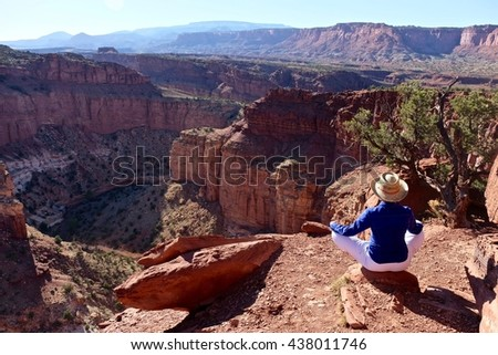 Woman Hiker in Yoga Pose Meditating by Canyon.  Goose Neck at Capitol Reef National park, Utah, USA.  - stock photo