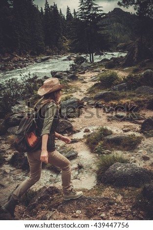 Woman hiker jumping on the stones near wild mountain river. - stock photo