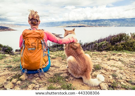 Woman hiker looking at sea with akita inu dog on seaside trail. Recreation and healthy lifestyle outdoors in summer mountains and sea nature. Beautiful inspirational landscape, trekking and activity. - stock photo