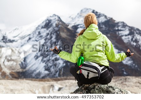 Woman Hiker Meditating on Rocks in Himalaya Mountains, Nepal. Young Girl Looking at Beautiful Inspirational Landscape. Recreation and Meditating in Yoga Pose Outdoors in High Mountains, Nepal.