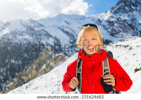 Woman hiker nordic walking in Himalaya Mountains in Nepal. Trekking on snow white winter nature, beautiful mountain landscape. - stock photo