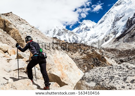Woman hiker nordic walking on footpath in Himalaya Mountains in Nepal. Trekking to Everest basecamp on rocky footpath in autumn nature, beautiful mountain landscape. - stock photo