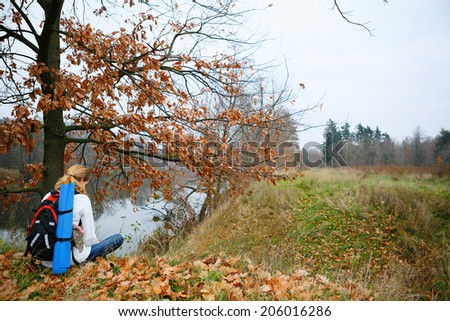 Woman hiker relax on the autumn riverside. Active Lifestyle
