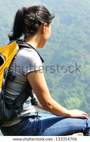 woman hiker sit rock at mountain top looking at the view
