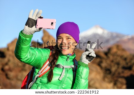 Woman hiker taking selfie photo using smartphone while hiking in winter jacket and clothing enjoying outdoor activity. Woman hiker taking self-portrait picture with smart phone camera. - stock photo