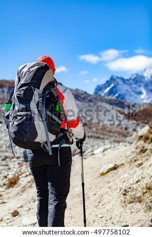 Woman hiker trekking with big backpack in Himalaya Mountains. Person on hiking trail backpacking in high mountains and inspirational landscape. Looking at beautiful mountain view.
