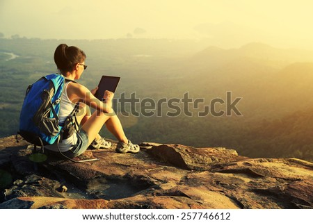 woman hiker use digital tablet at mountain peak cliff - stock photo