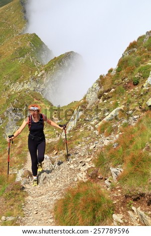 Woman hiker walking on alpine trail above the clouds - stock photo