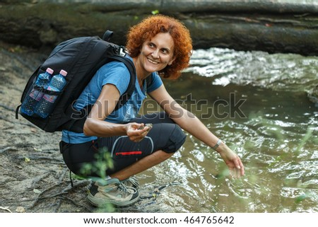 Woman hiker washing her hands in a mountain river