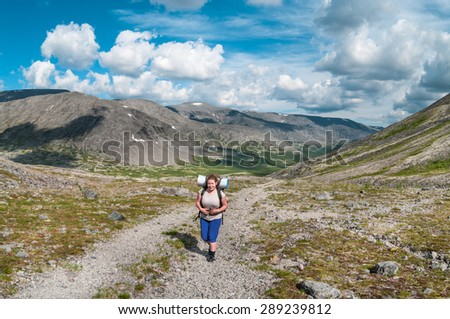 Woman hiker with backpack climbing the mountain road in summer season - stock photo