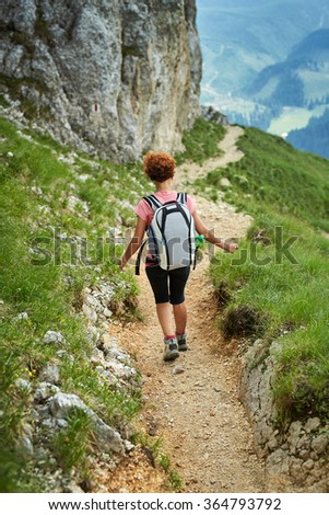 Woman hiker with backpack descending on a steep trail in the mountains - stock photo