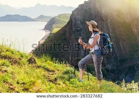 Woman hiking. Hike in the mountains. Woman traveler with backpack on beautiful summer landscape.   - stock photo