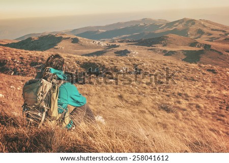 Woman hiking in beautiful nature, recreation and healthy lifestyle outdoors in wild. Hiker backpacker sitting on mountain top. - stock photo